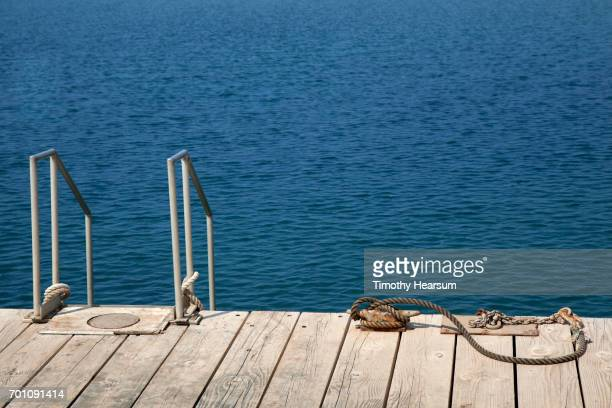 dock with ladder into the ocean and rope for boat tie-up - timothy hearsum stock-fotos und bilder