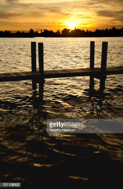 dock with sun setting through clouds in the background - timothy hearsum imagens e fotografias de stock