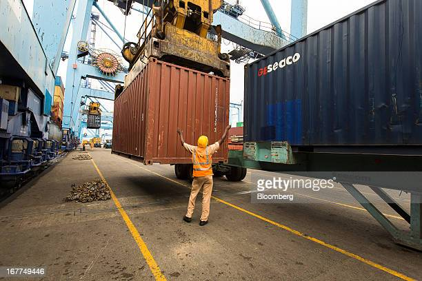 A dock worker for the Kenya Ports Authority a staterun company directs the unloading of shipping containers from freight ships at Mombasa port in...