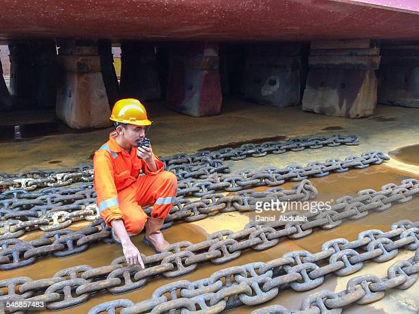Dock worker in a shipyard talking on a walkie talkie