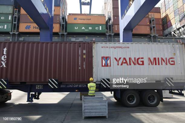 A dock worker removes safety bolts from a Yang Ming Marine Transport Corp shipping container at the terminal operated by Piraeus Container Terminal...