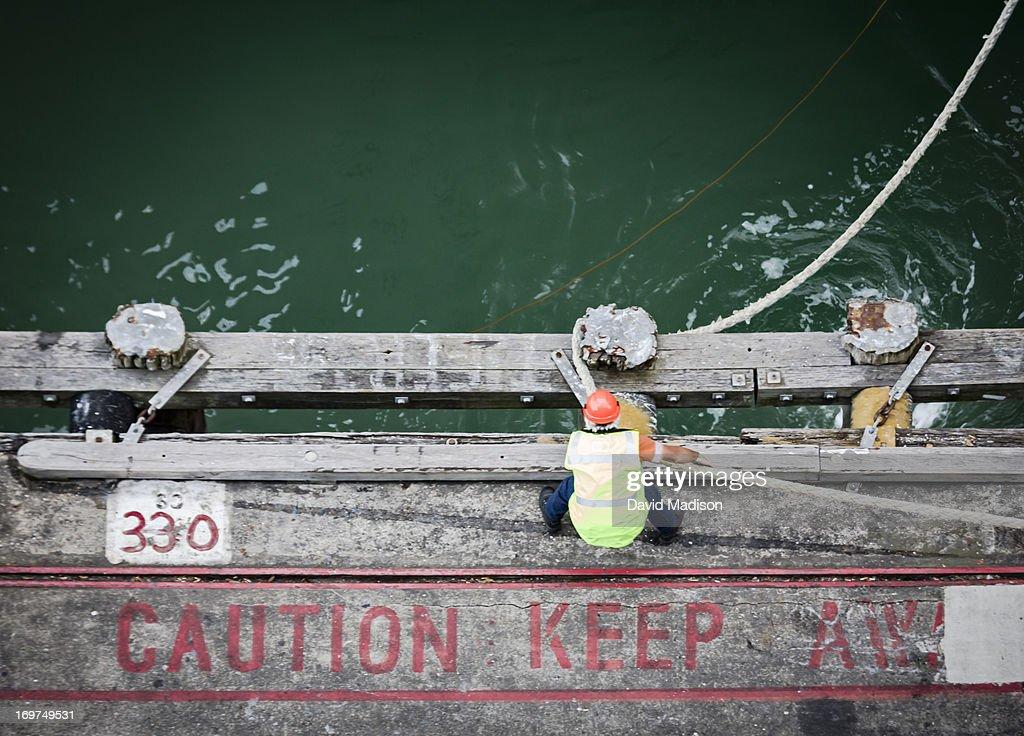 Dock worker tying hawser rope to pier bollard. : Stock Photo