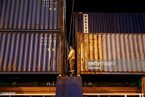 A dock worker unlocks a shipping container during unloading operations on a cargo ship at Pier 1 in the commercial shipping area at Piraeus Port...