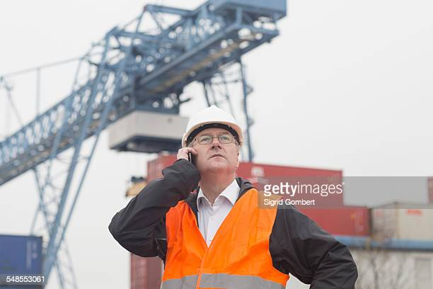 Dock worker using smartphone at port