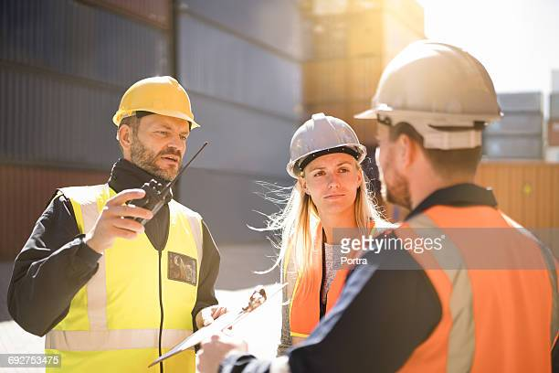 dock workers discussing in shipping yard - dock worker stock photos and pictures