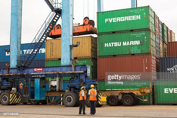 Dock workers for the Kenya Ports Authority a staterun company stand and watch as shipping containers are unloaded from freight ships at Mombasa port...