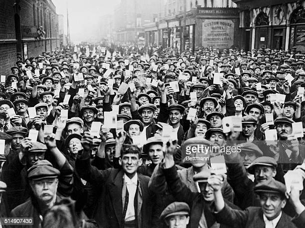 Dock workers hold up their union cards during a walkout which helped cripple Great Britain in the greatest strike in the history of the world The men...