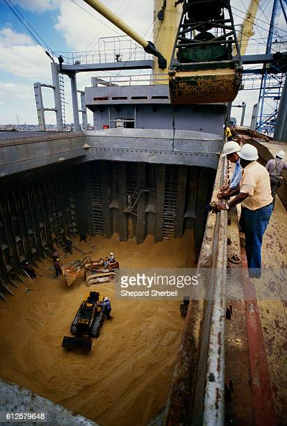 Dock workers in Baltimore watch as raw sugar, from the Caribbean, is unloaded in the hold of a ship in 1985.