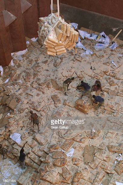 Dock workers load USdonated bags of wheat destined for Ethiopia onto trucks from inside the hold of an American cargo ship February 21 2003 in...