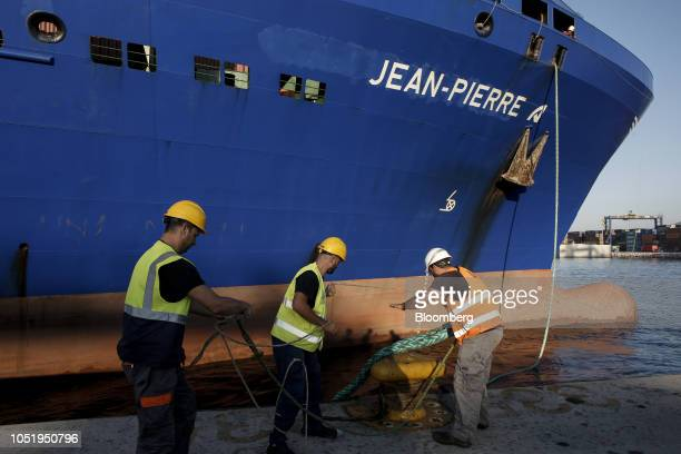 Dock workers secure the ropes of a cargo vessel at the container terminal operated by Piraeus Container Terminal SA at the Port of Piraeus in Piraeus...