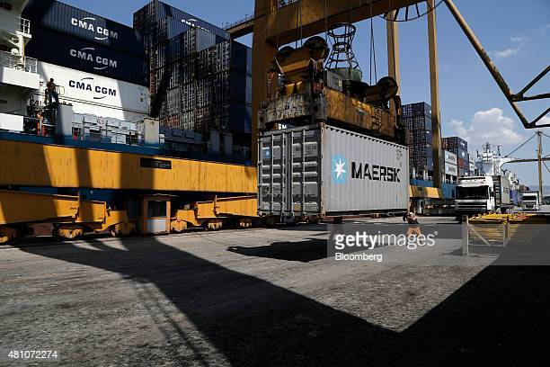 Dock workers stand beside an AP MoellerMaersk A/S shipping container as it is loaded onto cargo vessel Santa Bettina operated by Reederei ClausPeter...