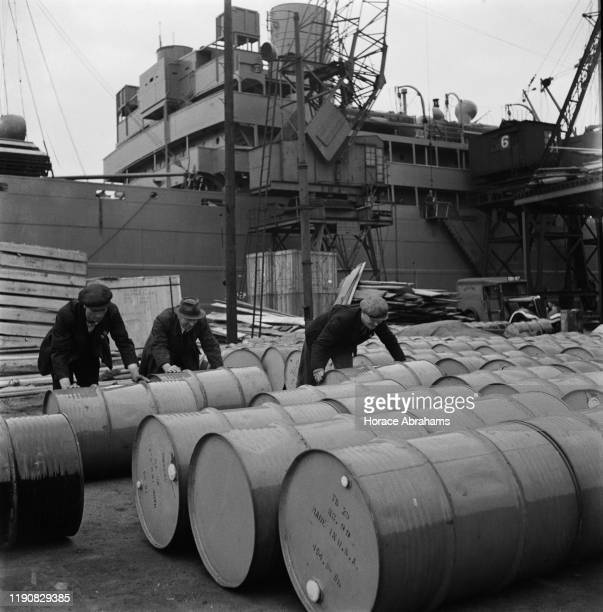 Dock workers unloading barrels from the USA at a dock in the UK during World War II June 1941