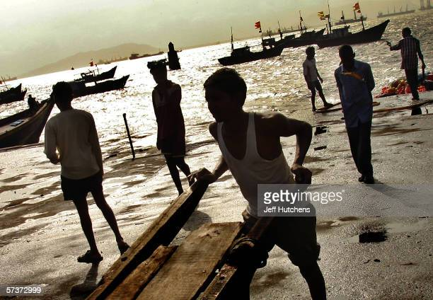 Dock workers wait for the ships to bring in their day's catch Emerging from one of the most deadly monsoon seasons in recent history, daily life gets...