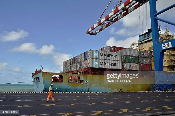 A docker passes by a container ship on May 5 2015 in the Doraleh harbour in Djibouti AFP PHOTO / CARL DE SOUZA