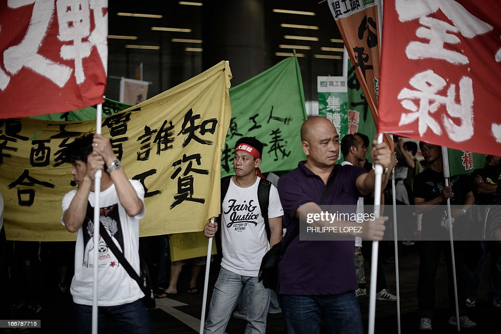 Dockers hold banners as they protest on the 21st day of their strike in Hong Kong on April 17, 2013 asking for an increase in pay and better working conditions. The Hong Kong International Terminals (HIT) which operates 12 berths, is a unit of tycoon Li Ka-shing's Hutchison Port Holdings Trust, part of the vast empire owned by Asia's richest man whose firms control about 70 percent of the in the city's port traffic. AFP PHOTO / Philippe Lopez