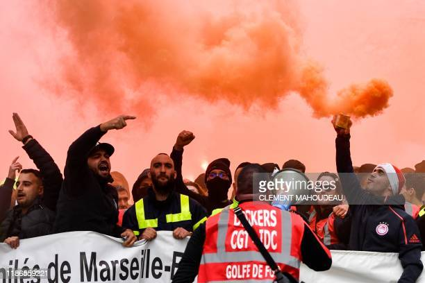 Dockers march with smoke bombs and hold a banner as they take part in a demonstration to protest against the pension overhauls in Marseille southern...