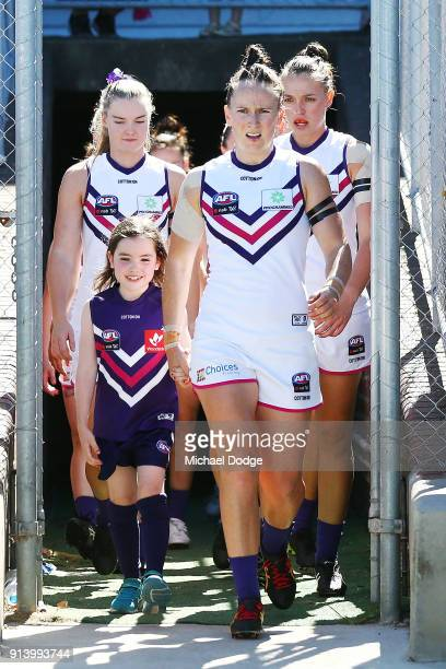 Dockers players walk out to the banner during the round one AFLW match between the Western Bulldogs and the Fremantle Dockers at Whitten Oval on...
