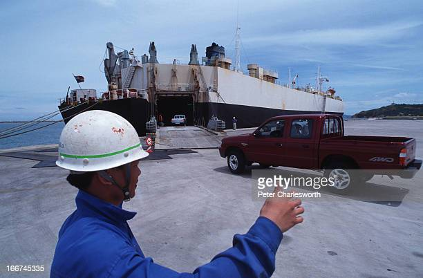 CHABANG CHONBURI THAILAND A dockworker directs Thai manufactured Mazda pickup trucks which are made for export onto a transporter ship moored to the...