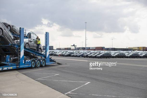 A dockworker prepares to unload Adam Opel AG automobiles from a vehicle transporter at the Port of Killingholme in Killlingholme UK on Thursday July...