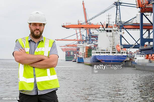 Dockworker standing in front of container ships in port