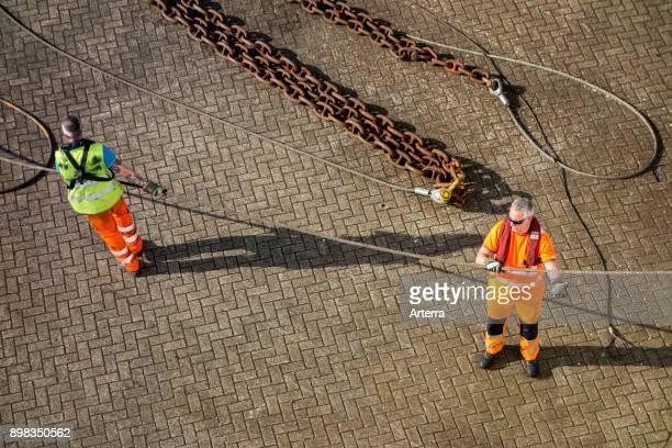 Dockworkers attaching moored ship's hawser to shoreside bitt on quay in seaport's dock