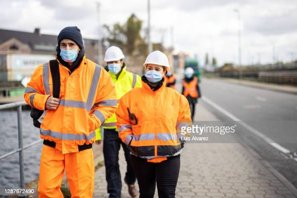 dockyard workers arriving at work with face masks - arrival stock pictures, royalty-free photos & images