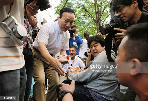 NTT DoCoMo Inc President Kaoru Kato distributes bread and apple juice to queueing customers in front of the NTT DoCoMo shop on September 20 2013 in...