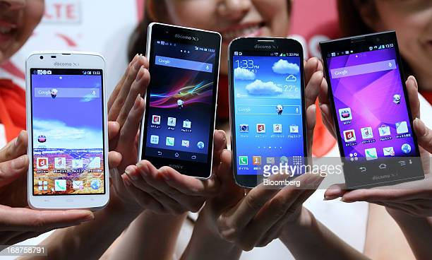 DoCoMo Inc.'s new smartphones are displayed, from left, Aquos Phone Zeta manufactured by Sharp Corp., Xperia A manufactured by Sony Mobile...