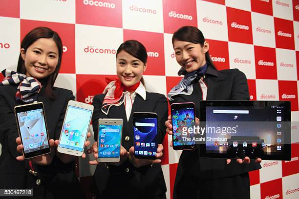 NTT DoCoMo staffs display new mobile phones during their unveiling on May 11 2016 in Tokyo Japan