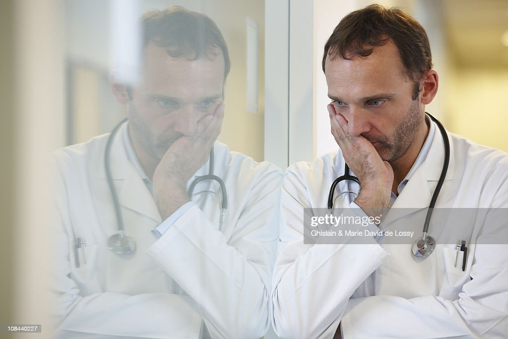 Doctor against a window, thinking : Stock Photo