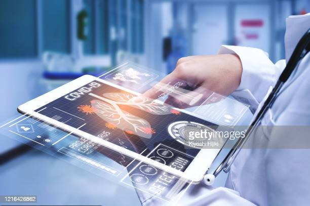 doctor analyzing covid-19 or coronavirus test result with futuristic tablet - 医療とヘルスケア ストックフォトと画像
