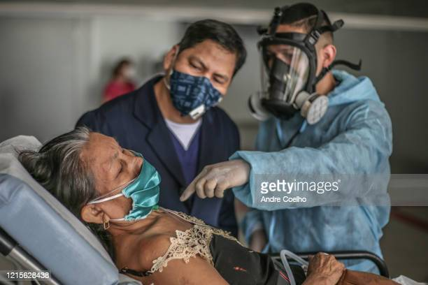 Doctor and a nurse talk about a woman infected by coronavirus as she arrives at the Gilberto Novaes Municipal Field Hospital on May 27, 2020 in...