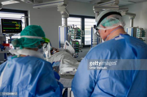 A doctor and a nurse wear protective suits masks goggles and gloves as they make the morning medical checks in the Intensive Care Unit for COVID19...