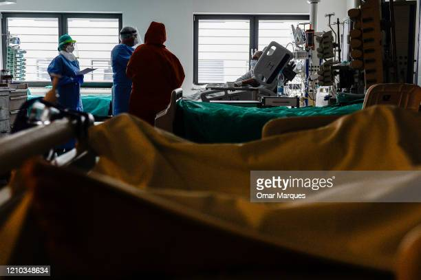 Doctor and a nurse wear protective, suits, masks, goggles and gloves as they speak to a conscious COVID-19 patient during the morning medical checks...