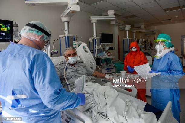 A doctor and a nurse wear protective suits masks goggles and gloves as they speak to a conscious COVID19 patient during the morning medical checks in...