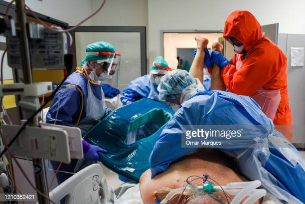 Doctor and a nurse wear protective, suits, masks, goggles and gloves as they turn up side down an unconscious COVID-19 patient in order to improve...