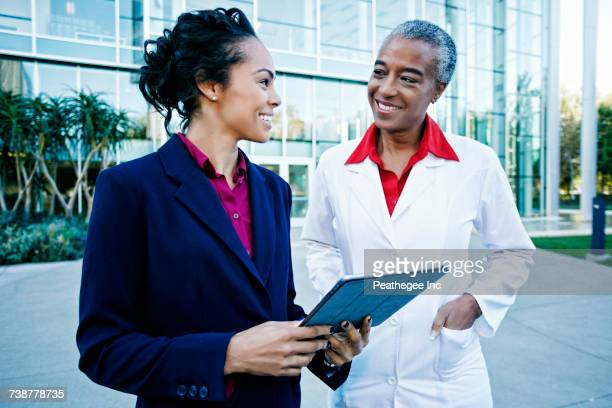 Doctor and administrator outdoors at hospital using digital tablet