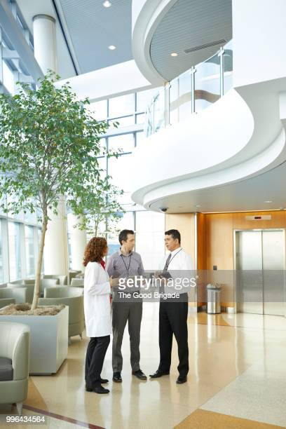 doctor and administrators talking in hospital lobby - medical building stock pictures, royalty-free photos & images