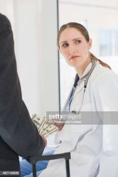 Doctor and businessman exchanging money in hospital