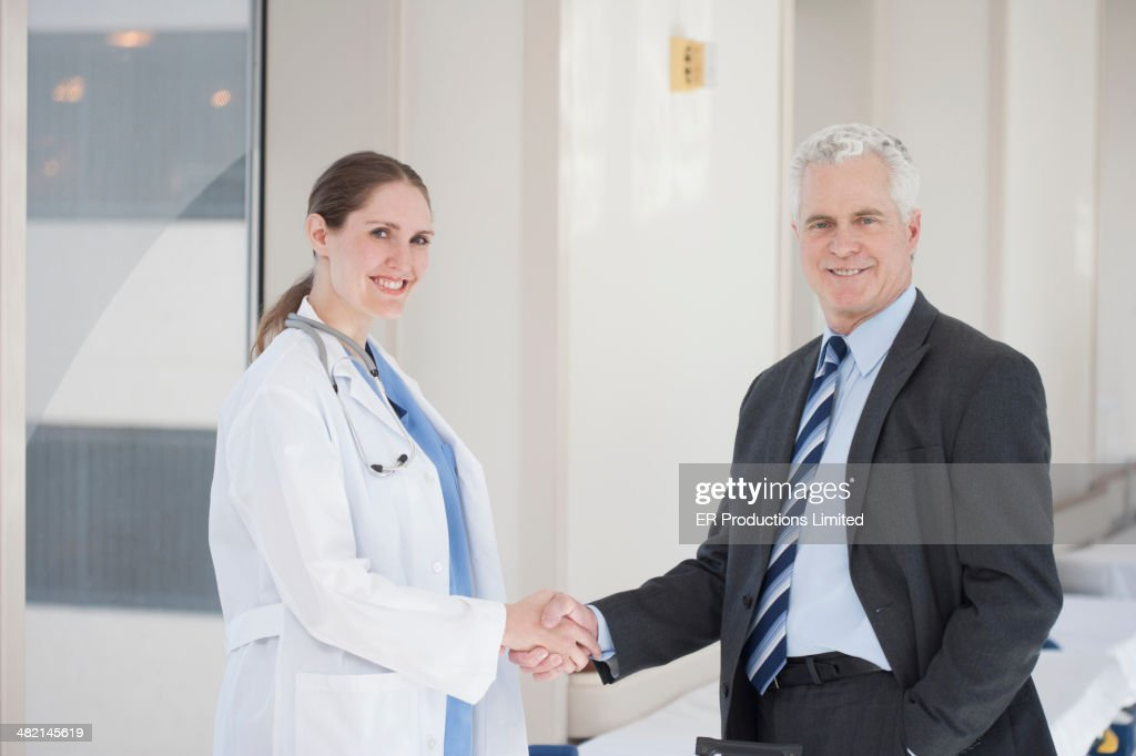 Doctor and businessman shaking hands in hospital : Stock Photo