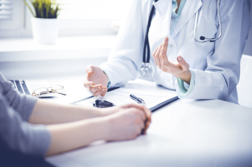 Doctor and  female patient sitting at the desk and talking  in clinic near window. Medicine and health care concept. Green is main color 1148334988