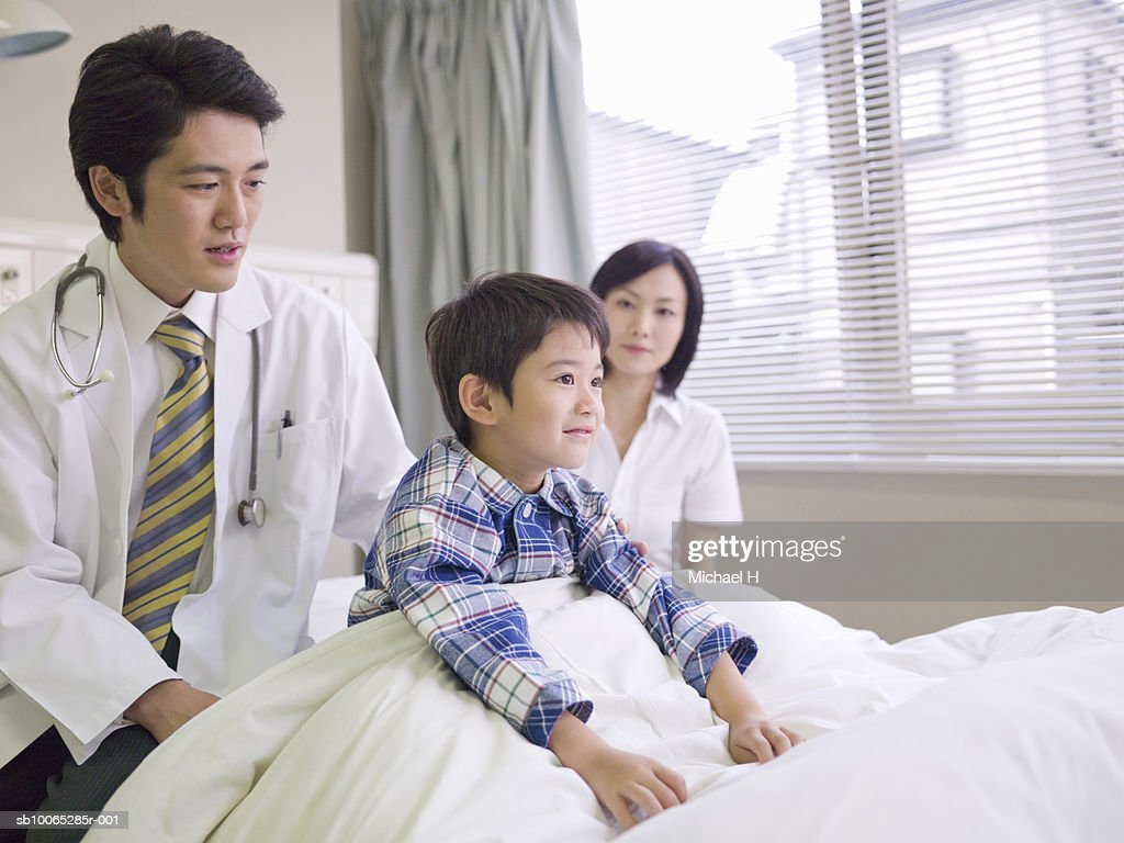 Doctor and mother with boy (5-6) in hospital bed : Foto stock