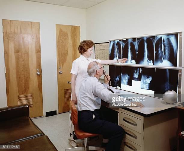 A doctor and nurse at Greenville Memorial Hospital look over a patient's xrays Doctor uses a dictaphone