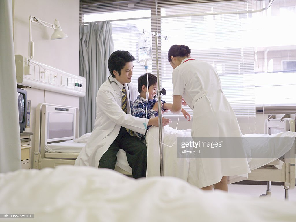 Doctor and nurse attending boy (5-6) in hospital bed : Foto stock