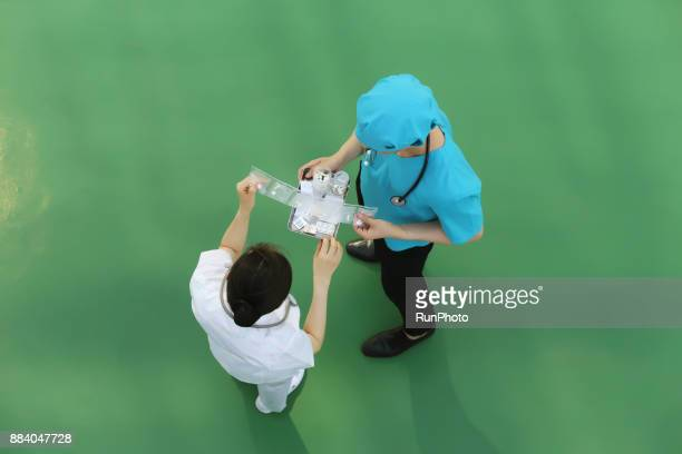 Doctor and nurse holding pack of medicine in hands