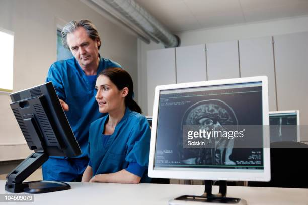 doctor and nurse looking at mr images - brain  stock pictures, royalty-free photos & images