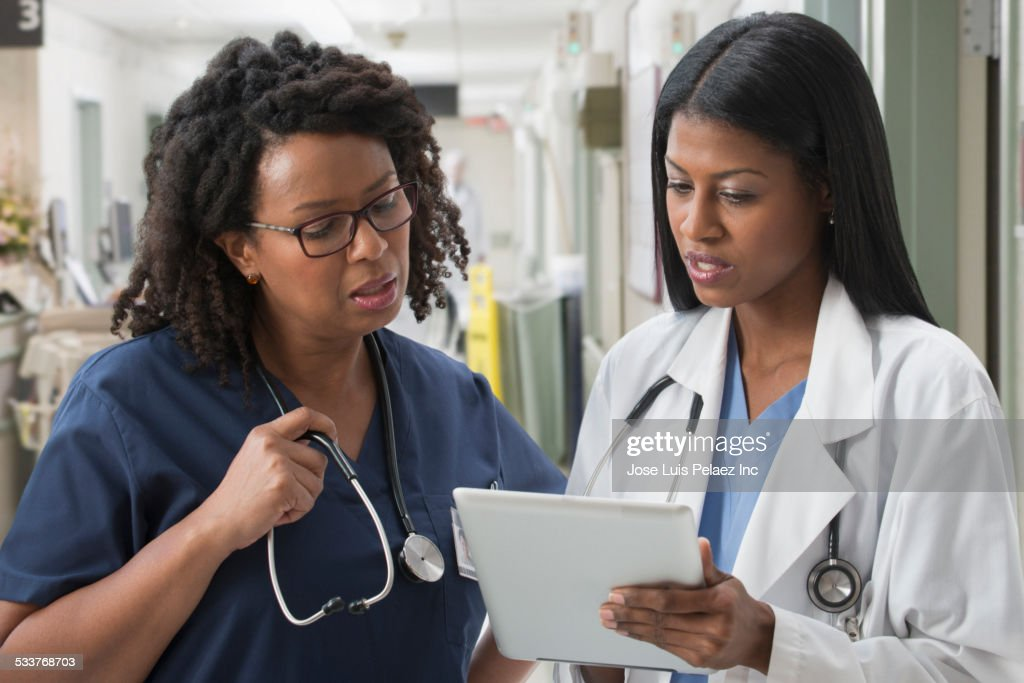 Doctor and nurse reviewing medical chart in hospital : Foto stock
