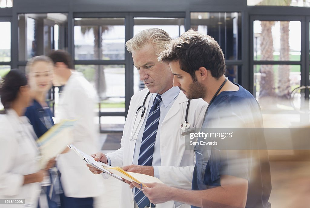 Doctor and nurse reviewing medical record in hospital : Stock Photo