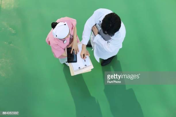 Doctor and nurse reviewing patient files on digital tablet