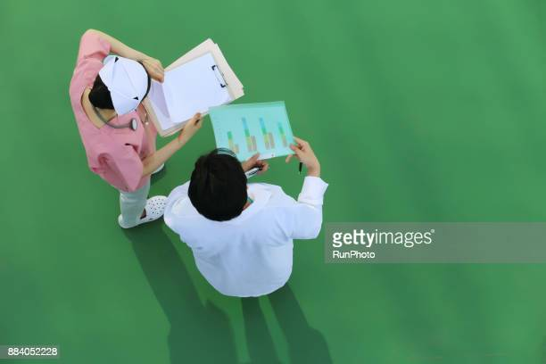 Doctor and  nurse reviewing patient files